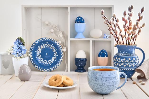 Tasse kaffee und kekse auf weißem tisch mit bündel weidenkätzchen und frühlingsdekorationen