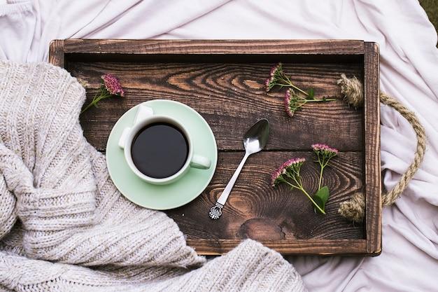 Tasse kaffee und kerze auf rustikalem hölzernen serviertablett und warmem wollpullover stricken