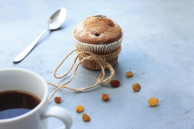 Tasse kaffee und kleiner kuchen mit rosinen zum frühstück auf tabelle