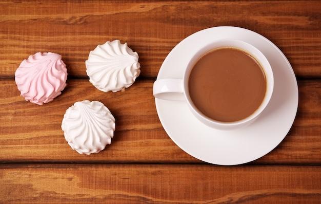 Tasse kaffee und kuchen auf holzhintergrund.