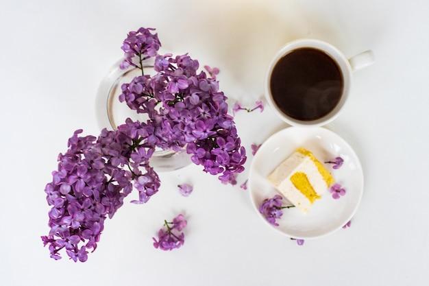 Tasse kaffee und kuchenhörner ausstillleben mit einem strauß flieder auf einem weißen tisch, eine tasse kaffee, ein teller mit einem stück kuchen. internationaler frauentag, 8. märz