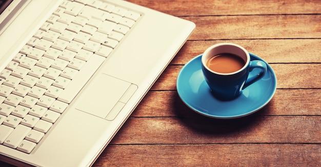 Tasse kaffee und laptop auf holztisch.