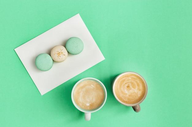 Tasse kaffee und leckere makronen zum frühstück auf minzpapier, morgendlichen heißen getränken und süßigkeiten