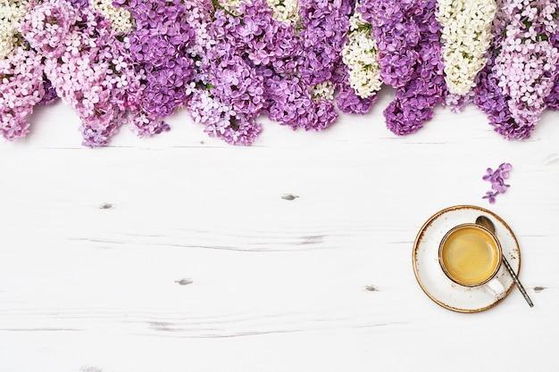 Tasse kaffee und lila blumen grenzen an weißen hölzernen hintergrund an
