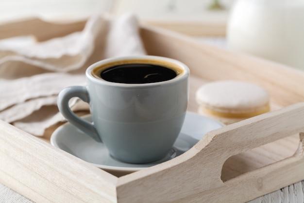 Tasse kaffee und macaron-kuchen auf tablett auf weißem holztisch