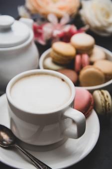 Tasse kaffee und makronen auf farbigem gelbem tisch.