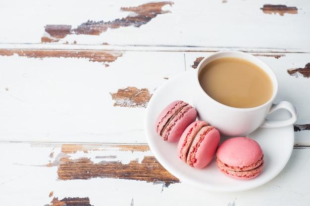 Tasse kaffee- und makronenplätzchen auf einer platte auf einem weißen hintergrund. kopieren sie platz