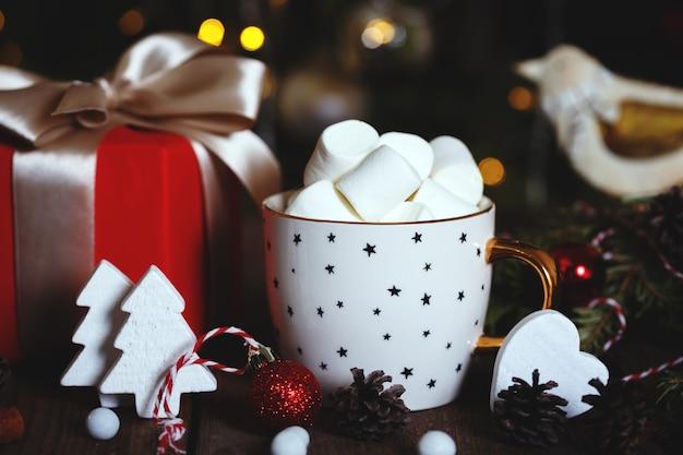 Tasse kaffee und marshmallows. geschenke, lebkuchen und weihnachtsschmuck