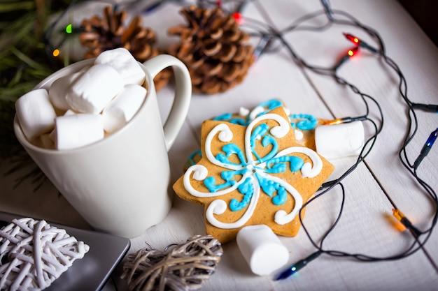 Tasse kaffee und marshmallows. lebkuchen und weihnachtsschmuck