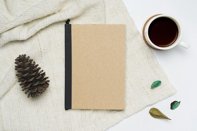 Tasse kaffee und notizbuch auf braunem garnhintergrund