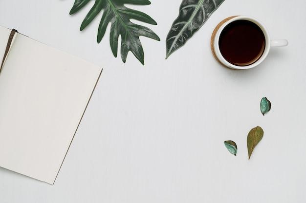 Tasse kaffee und notizbuch auf weißem hölzernem hintergrund mit tropischen monstera blättern