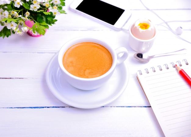 Tasse kaffee und notizbuch mit einem roten bleistift