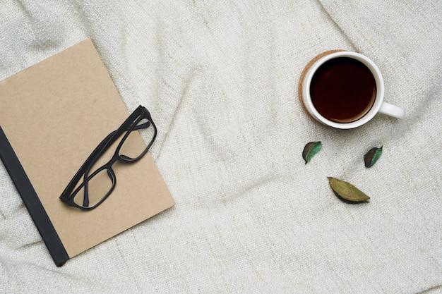 Tasse kaffee und notizbuch mit gläsern auf braunem garnhintergrund.