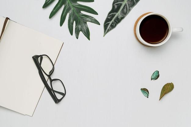 Tasse kaffee und notizbuch mit minimaler ebenenlage der gläser