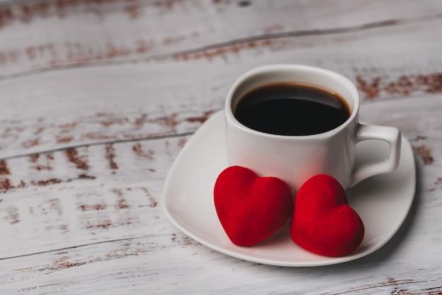Tasse kaffee und paare von roten valentinstagherzen auf weißem holztisch. das konzept der grußkarte