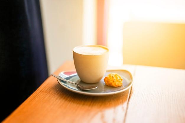 Tasse kaffee und plätzchen auf holztisch