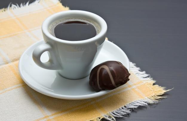 Tasse kaffee und praline auf dem tisch