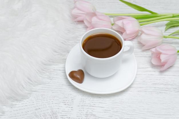 Tasse kaffee und rosa tulpen.