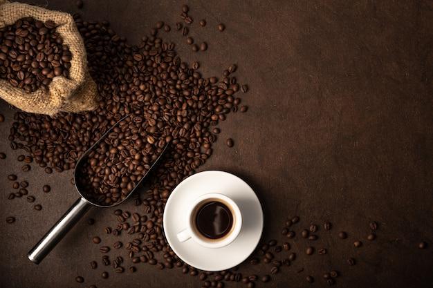 Tasse kaffee und schaufel auf braunem hintergrund. kopierbereich der draufsicht
