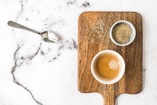 Tasse kaffee und schüssel zucker auf weißem marmor hintergrund