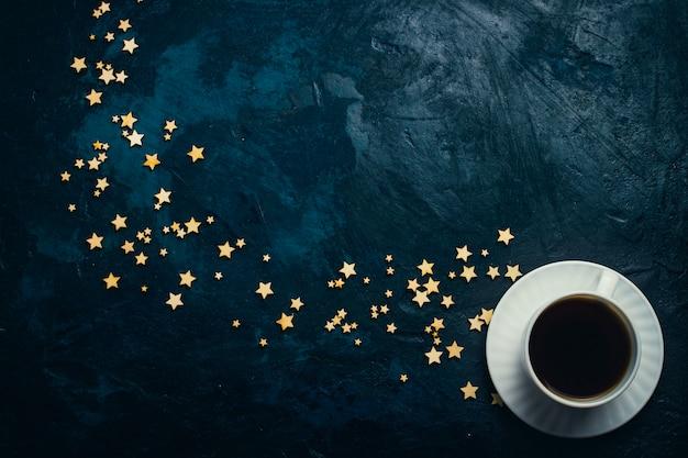 Tasse kaffee und sterne auf einem dunkelblauen hintergrund. konzept des sternenhimmels und des kaffees.