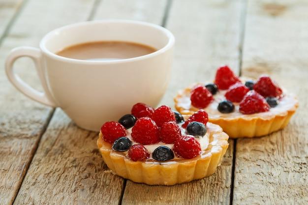 Tasse kaffee und süße kuchen mit beeren