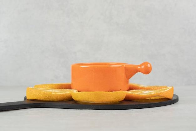 Tasse kaffee und teller mit orangenscheiben auf dunklem brett