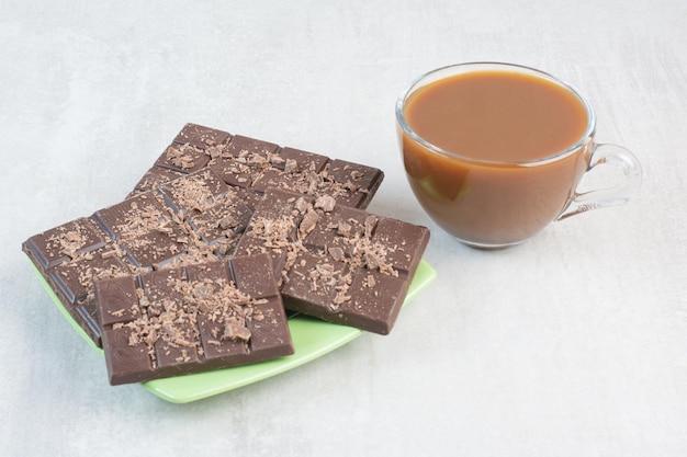 Tasse kaffee und teller mit schokoriegeln auf steinhintergrund. foto in hoher qualität