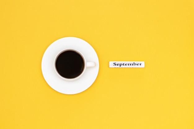 Tasse kaffee und text september auf gelbem grund