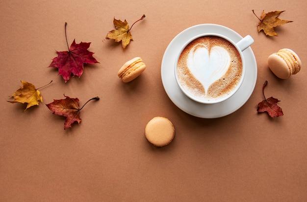 Tasse kaffee und trockene blätter auf braunem hintergrund. flache lage, draufsicht, kopierraum