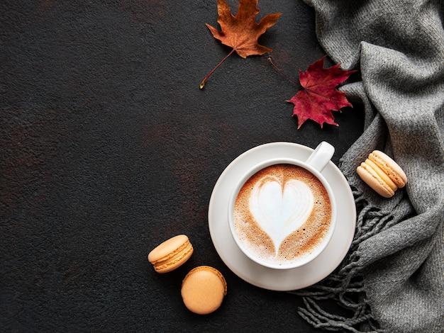 Tasse kaffee und trockene blätter auf schwarzem beton.