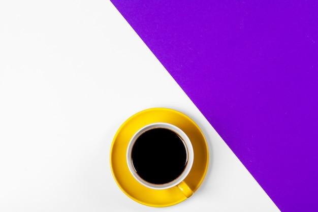 Tasse kaffee und untertasse auf farbigem hintergrund