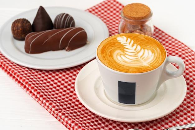 Tasse kaffee und untertasse mit pralinen auf holztisch