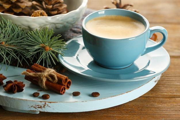 Tasse kaffee und weihnachtsbaumast auf holzmatte