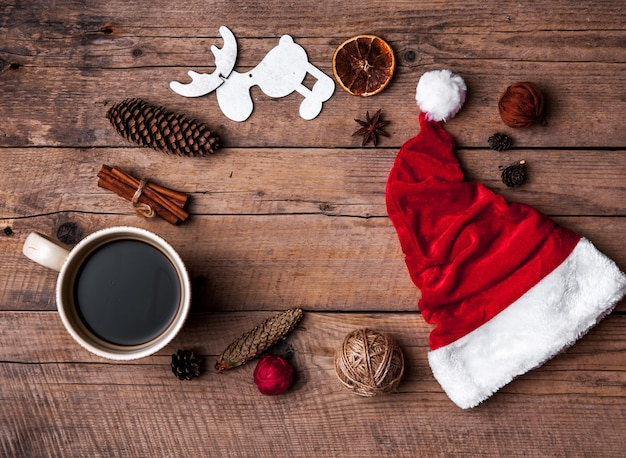 Tasse kaffee und weihnachtsmütze, weihnachtsset, geschenk und weihnachtsbaum.