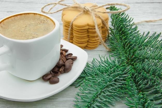 Tasse kaffee und weihnachtsplätzchen, auf dem hintergrund von tannenzweigen. der urlaub kommt zu uns.
