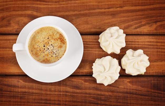 Tasse kaffee und weiße kuchen auf holzuntergrund.