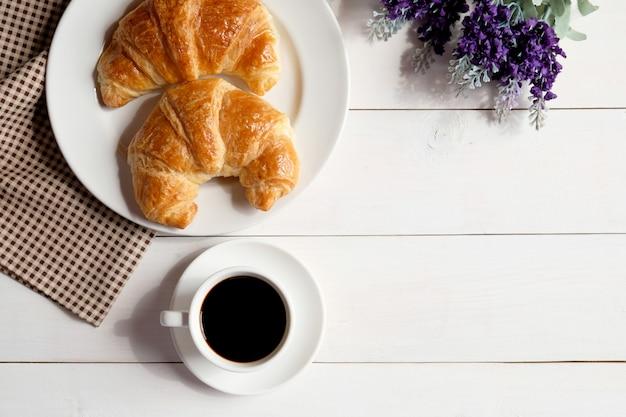 Tasse kaffee und weißer teller mit hörnchen auf weißem hölzernem hintergrund.