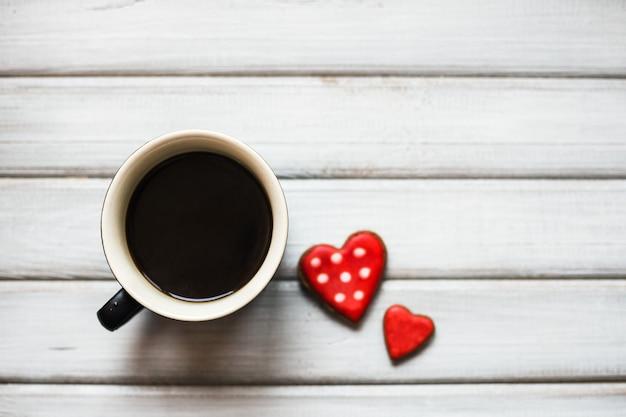 Tasse kaffee und zwei herzförmige kekse lebkuchen