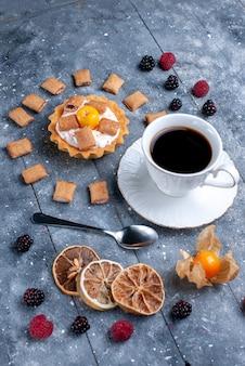 Tasse kaffee von oben mit cremigem kuchenkissen bildete kekse zusammen mit beeren auf grauem schreibtisch, beerenkeksplätzchen