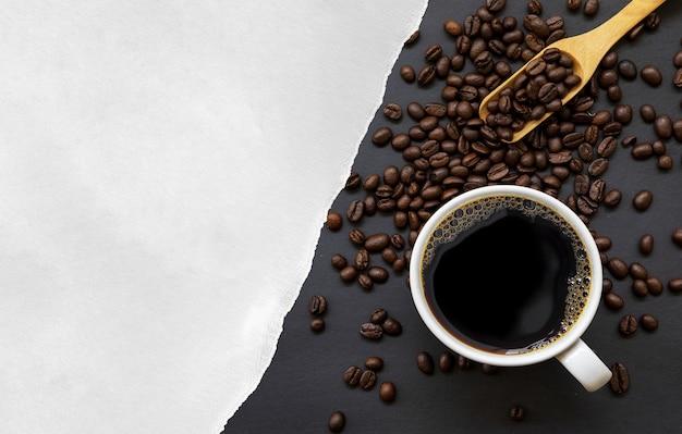 Tasse kaffee, weißes papier und bohne auf schwarzem holztischhintergrund. draufsicht