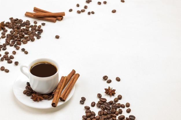 Tasse kaffee, zimtstangen und sternanis auf untertasse. körner von kaffee und zimt auf dem tisch. weißer hintergrund. ansicht von oben. platz kopieren