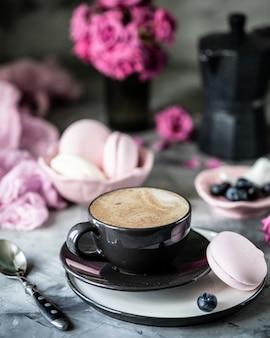 Tasse kaffee zum frühstück mit marshmallows in form von makronenkuchen in einer schwarzen schüssel auf einem dunklen tisch und mit blumen in einem glas