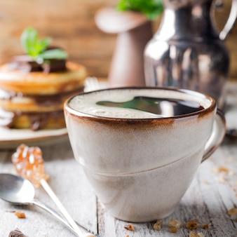 Tasse kaffee zum frühstück mit pfannkuchen.