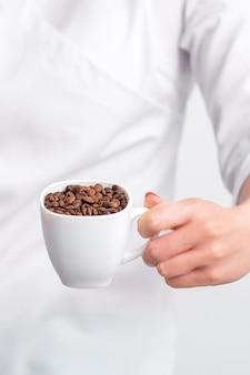 Tasse kaffeebohnen in weiblicher hand