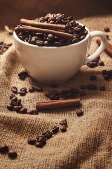 Tasse, kaffeebohnen und zimtstangen