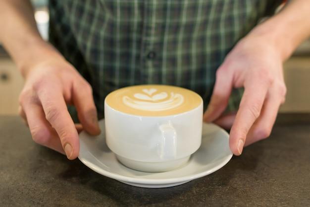 Tasse kaffeekunst mit den händen des männlichen barista