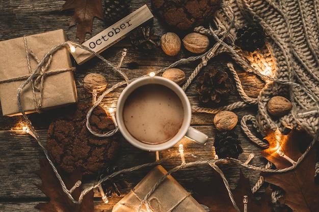Tasse kakao, girlande, kekse, nüsse, getrocknetes herbstlaub auf holztisch