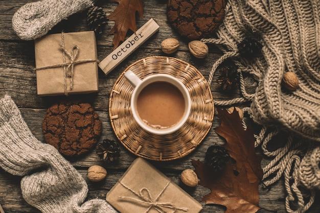 Tasse kakao, kekse, nüsse, getrocknetes herbstlaub auf holztisch