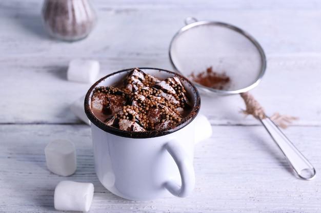 Tasse kakao mit marshmallows auf holz